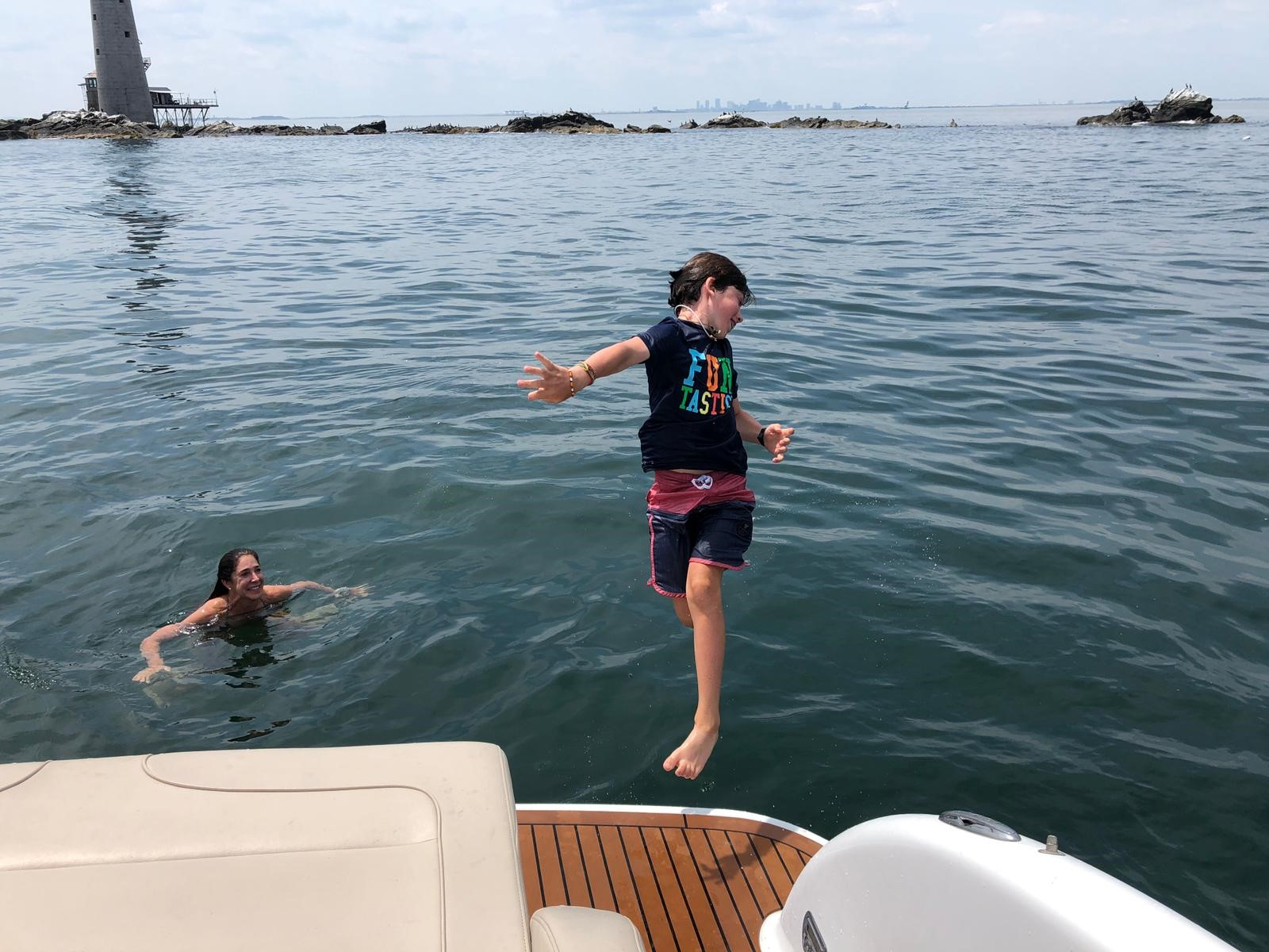 kid jumping off the back of a princess yacht